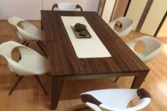 dunkler Tisch mit Designstühlen in weiß
