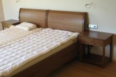 Bett mit dunklem Holz und Beistelltisch